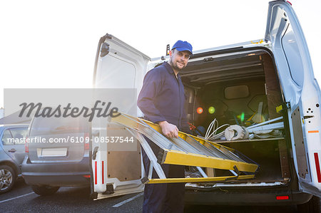 Portrait of handyman loading a ladder Stock Photo - Premium Royalty-Free, Image code: 6109-08537544
