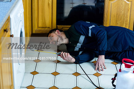 Pest control man spraying pesticide Stock Photo - Premium Royalty-Free, Image code: 6109-08537550