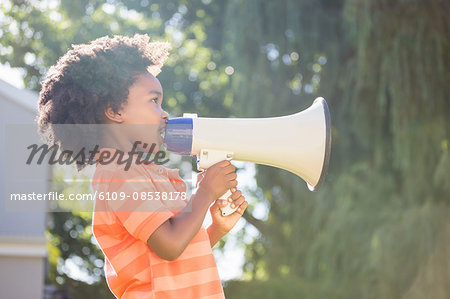 Cute mixed-race boy speaking on a megaphone Stock Photo - Premium Royalty-Free, Image code: 6109-08538178
