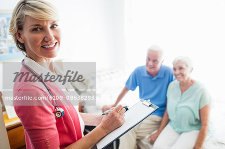Nurse writing on clipboard and senior couple sitting on a bed Stock Photo - Premium Royalty-Free, Image code: 6109-08538293