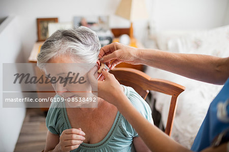 Nurse putting hearing aid to a senior woman Stock Photo - Premium Royalty-Free, Image code: 6109-08538492