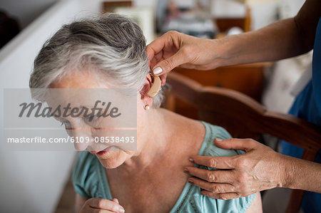 Nurse putting hearing aid to a senior woman Stock Photo - Premium Royalty-Free, Image code: 6109-08538493