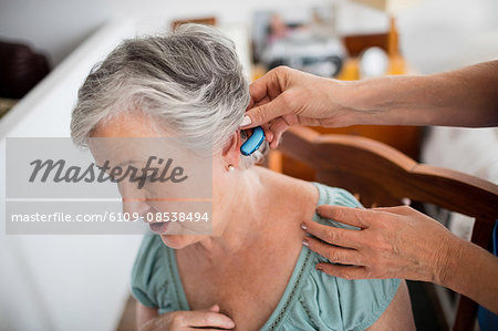 Nurse putting hearing aid to a senior woman Stock Photo - Premium Royalty-Free, Image code: 6109-08538494