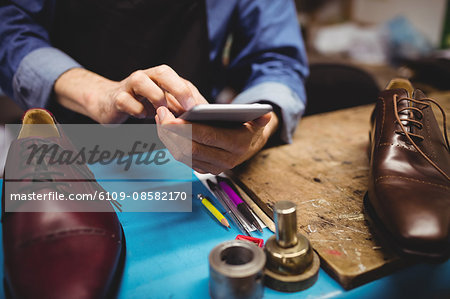Close up of cobbler typing on his mobile phone Stock Photo - Premium Royalty-Free, Image code: 6109-08582170