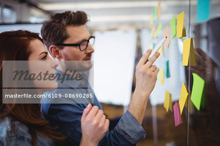 Creative business people looking at sticking notes on glass in office Stock Photo - Premium Royalty-Free, Image code: 6109-08690285