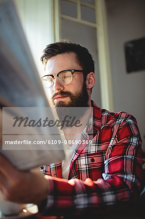 Young customer wearing eyeglasses reading newspaper at coffee shop