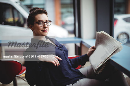 Portrait of businesswoman holding newspaper in cafe