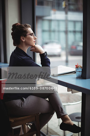 Businesswoman sitting by table in cafe