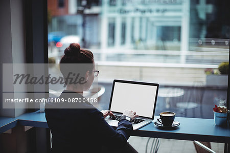 Woman using laptop on table in cafe