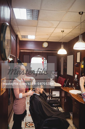 Man getting his hair trimmed with trimmer in barber shop Stock Photo - Premium Royalty-Free, Image code: 6109-08705384