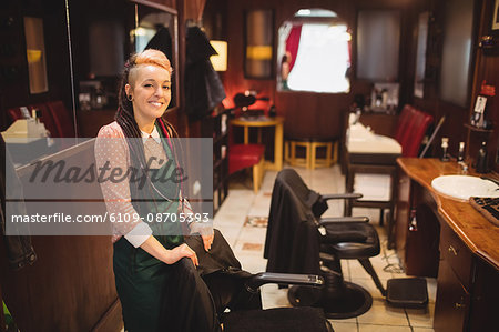 Portrait of smiling female barber standing in barber shop Stock Photo - Premium Royalty-Free, Image code: 6109-08705393