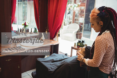 Man receiving a face massage from female barber in barber shop Stock Photo - Premium Royalty-Free, Image code: 6109-08705397