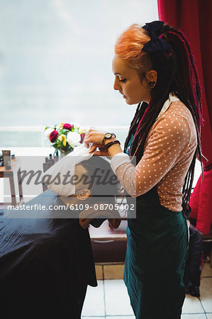 Barber applying a hot towel on a client face in barber shop Stock Photo - Premium Royalty-Free, Image code: 6109-08705402