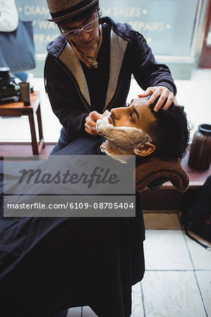 Man getting his beard shaved with shaving brush in barber shop Stock Photo - Premium Royalty-Free, Image code: 6109-08705404