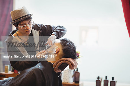 Man getting his beard shaved with razor in barber shop Stock Photo - Premium Royalty-Free, Image code: 6109-08705418