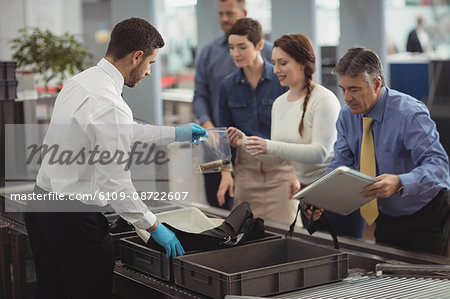 Commuter collecting their bags from the security counter at airport Stock Photo - Premium Royalty-Free, Image code: 6109-08722607