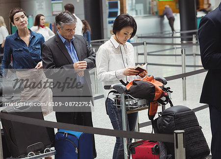 Passengers waiting in queue at a check-in counter with luggage inside the airport terminal Stock Photo - Premium Royalty-Free, Image code: 6109-08722752