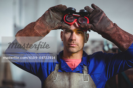 Male welder holding welding goggles in workshop Stock Photo - Premium Royalty-Free, Image code: 6109-08722814