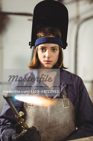 Female welder holding welding torch in workshop Stock Photo - Premium Royalty-Free, Image code: 6109-08722902