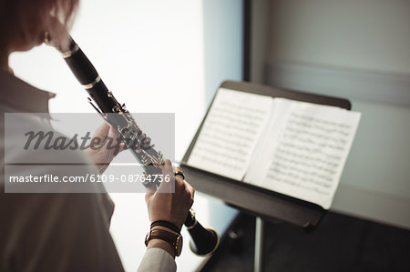 Mid-section of woman playing a clarinet in music school Stock Photo - Premium Royalty-Free, Image code: 6109-08764736