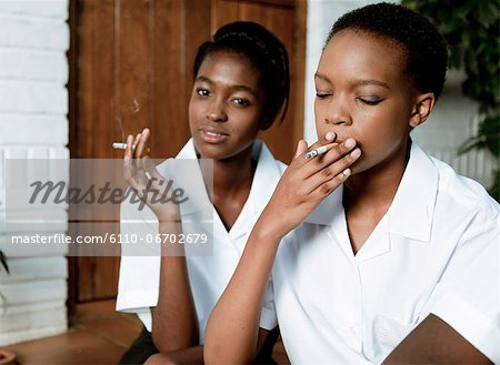 Two African teenage girls sit outside smoking cigarettes Stock Photo - Premium Royalty-Free, Image code: 6110-06702679