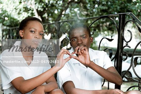 Two African teenagers sit together outside, smoking cigarettes Stock Photo - Premium Royalty-Free, Image code: 6110-06702683