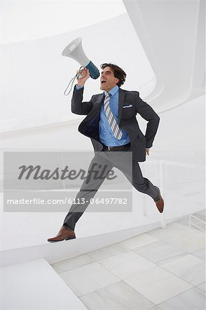 Leaping businessman with bullhorn Stock Photo - Premium Royalty-Free, Image code: 6113-06497782