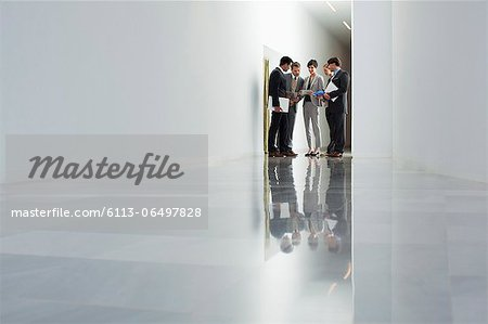 Business people meeting in corridor Stock Photo - Premium Royalty-Free, Image code: 6113-06497828