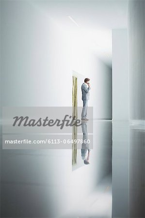 Businessman on cell phone in corridor Stock Photo - Premium Royalty-Free, Image code: 6113-06497860