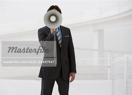 Portrait of businessman with bullhorn Stock Photo - Premium Royalty-Free, Image code: 6113-06497947