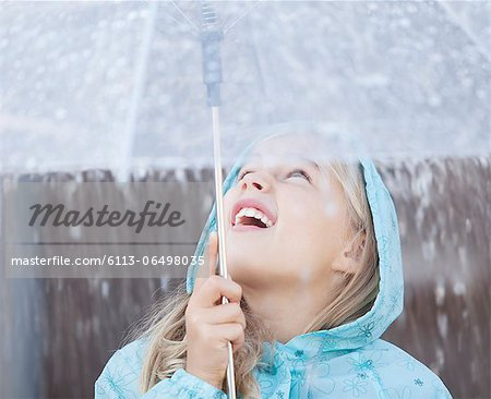 Close up of girl under umbrella looking up at downpour Stock Photo - Premium Royalty-Free, Image code: 6113-06498035