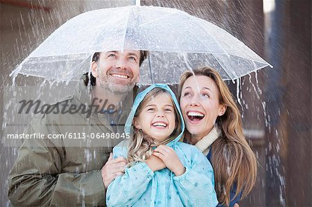 Enthusiastic family under umbrella in downpour Stock Photo - Premium Royalty-Free, Image code: 6113-06498045
