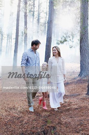 Happy family holding hands and walking in woods Stock Photo - Premium Royalty-Free, Image code: 6113-06498046