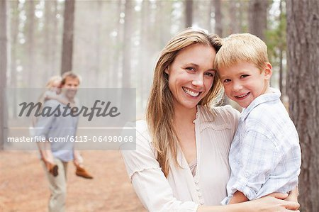 Portrait of smiling mother holding son in woods Stock Photo - Premium Royalty-Free, Image code: 6113-06498068