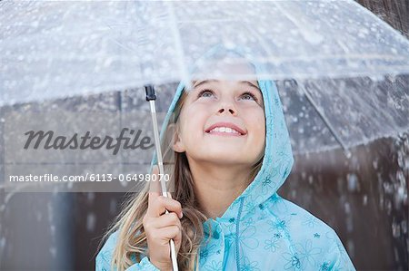 Close up of smiling girl under umbrella in downpour Stock Photo - Premium Royalty-Free, Image code: 6113-06498070