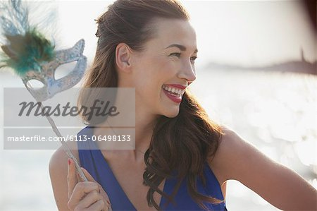 Close up of smiling woman holding mask Stock Photo - Premium Royalty-Free, Image code: 6113-06498133
