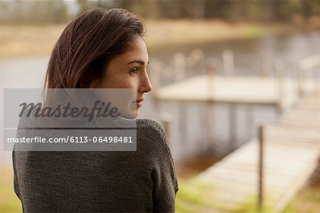 Pensive woman at lakeside Stock Photo - Premium Royalty-Free, Image code: 6113-06498481