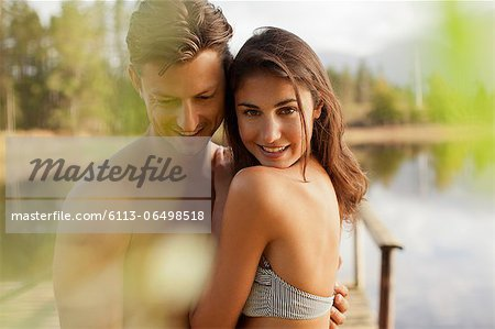 Portrait of smiling couple hugging at lakeside Stock Photo - Premium Royalty-Free, Image code: 6113-06498518