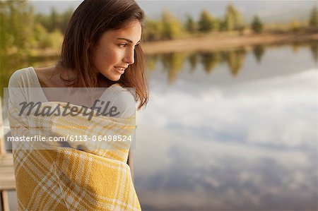 Smiling woman wrapped in blanket at lakeside Stock Photo - Premium Royalty-Free, Image code: 6113-06498524