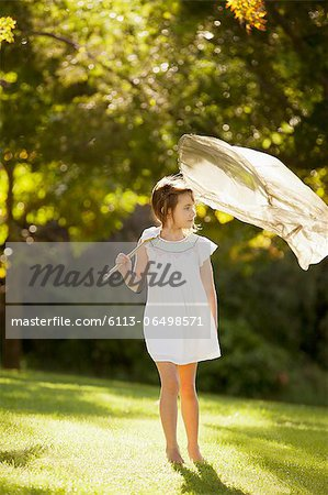 Girl carrying butterfly net in grass Stock Photo - Premium Royalty-Free, Image code: 6113-06498571