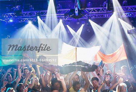 Man crowd surfing at concert Stock Photo - Premium Royalty-Free, Image code: 6113-06498592