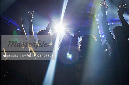 Spotlight over crowd dancing on dance floor
