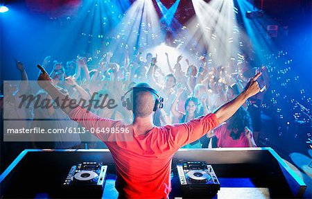 DJ with arms outstretched overlooking dance floor Stock Photo - Premium Royalty-Free, Image code: 6113-06498596