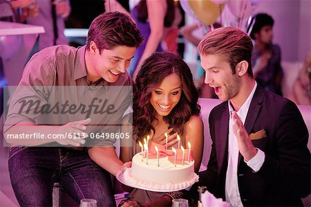 Friends with birthday cake in nightclub Stock Photo - Premium Royalty-Free, Image code: 6113-06498605