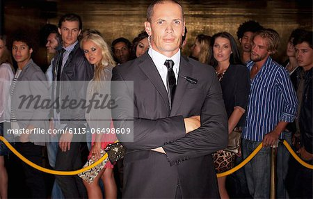 Portrait of serious bouncer with arms crossed in front of queue at nightclub Stock Photo - Premium Royalty-Free, Image code: 6113-06498609