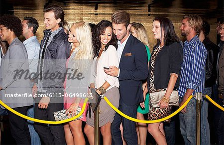 Couple with cell phone standing in queue outside nightclub Stock Photo - Premium Royalty-Free, Image code: 6113-06498613