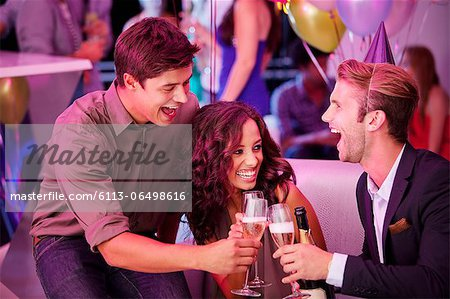 Enthusiastic friends toasting champagne flutes in nightclub Stock Photo - Premium Royalty-Free, Image code: 6113-06498616