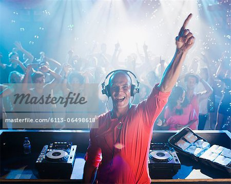 Portrait of enthusiastic DJ with arm raised and people on dance floor in background Stock Photo - Premium Royalty-Free, Image code: 6113-06498618
