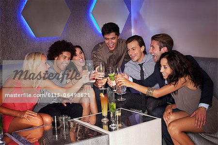 Friends toasting cocktails in nightclub Stock Photo - Premium Royalty-Free, Image code: 6113-06498621