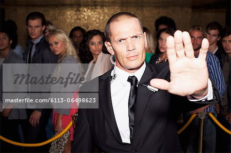 Portrait of bouncer with arm outstretched outside nightclub Stock Photo - Premium Royalty-Free, Image code: 6113-06498623